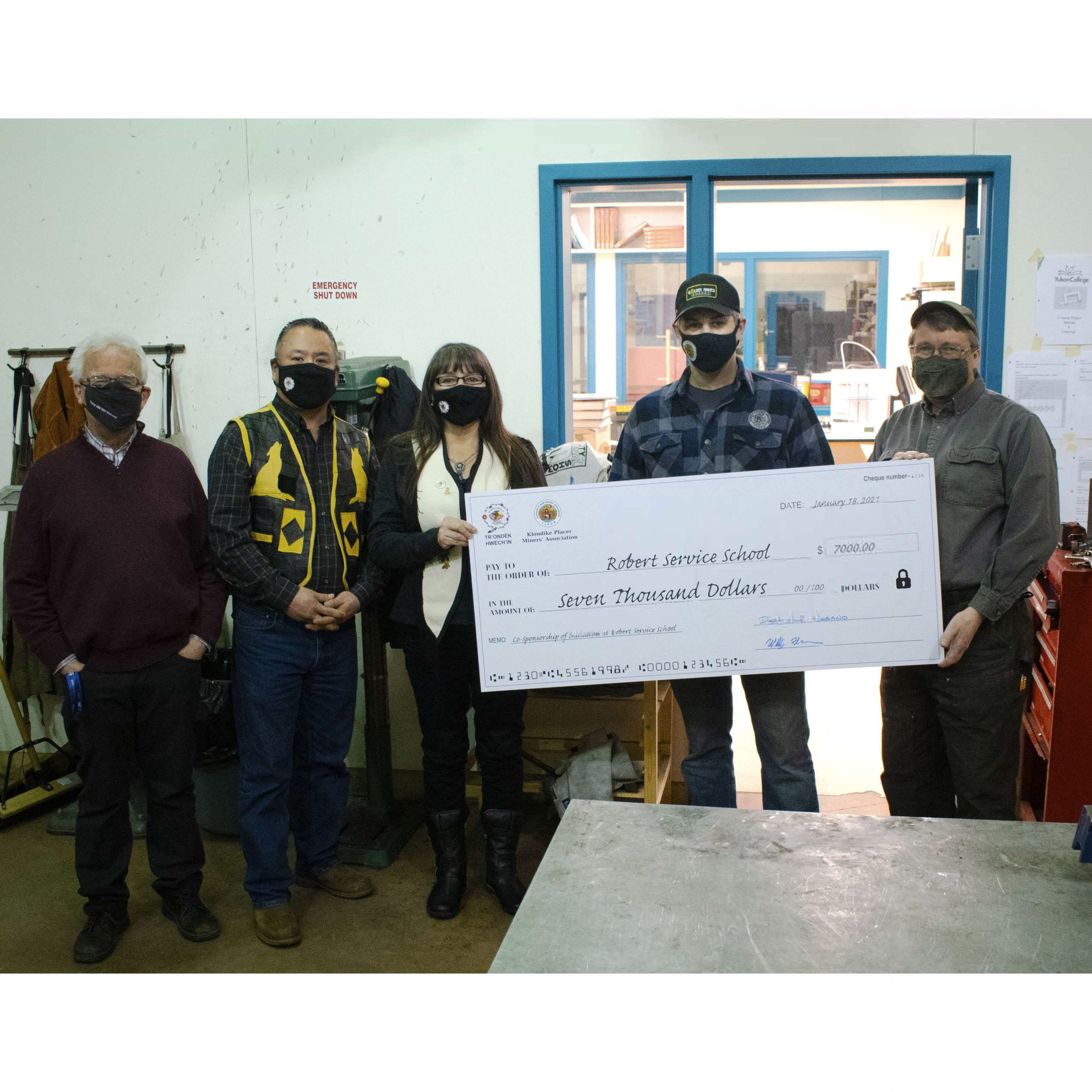 Chief Joseph, Deputy Chief Nagano, and KPMA President Will Fellers presenting a cheque to the Robert Service Secondary School principal Brian Lewthwaite and teacher Peter Menzies.